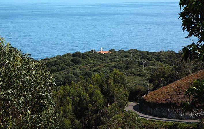 Faro de Pimiango, al fondo de la zona de acantilados. Foto: Turismo de Asturias